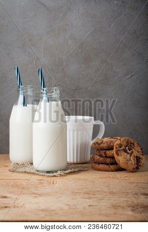 Two Bottles Of Milk And Chocolate Chip Cookies On Dark Background With Copy Space.