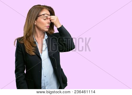 Middle age business woman with sleepy expression, being overworked and tired, rubbes nose because of weariness