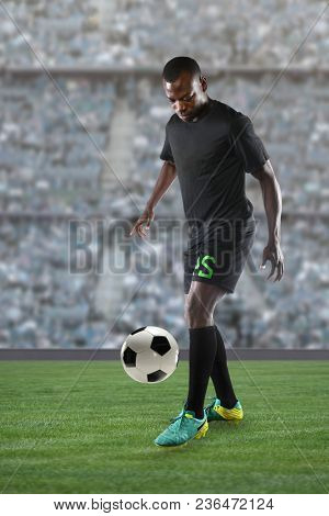 African American soccer player controlling ball inside large stadium