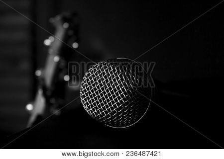 Microphone Closeup With Bass Guitar In The Background