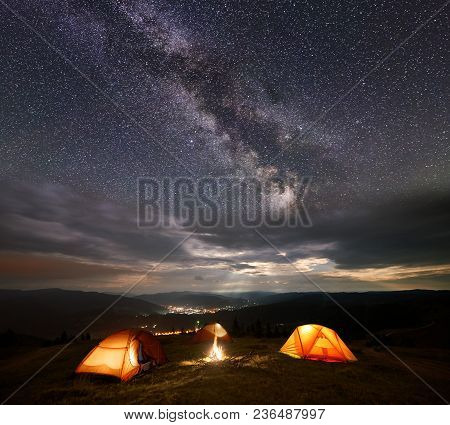 Night Camping. Three Illuminated Orange Tents In The Mountains At Night Under Starry Sky, Milky Way
