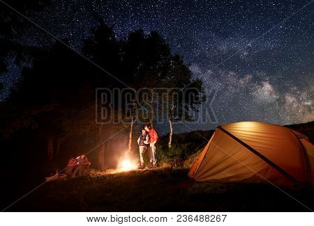Two Young Couples Tourists At Campfire Under The Bright Starry Sky Near The Illuminated Orange Tent