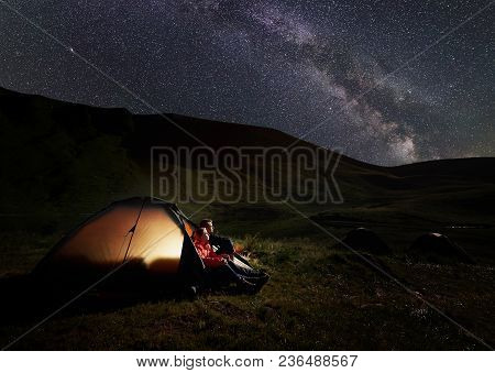 Man And Woman Having A Rest At Night Camping In The Carpathians Mountains Near Dogyaska Lake, Sittin