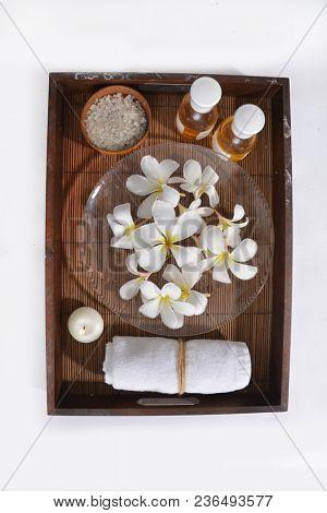 Many white frangipani,salt in bowl,bottle oil, candle, towel, on mat
