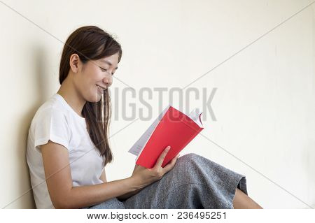 Beautiful Woman Of A Student Sitting With Laptop And Relaxing In The Garden. Education Concept.