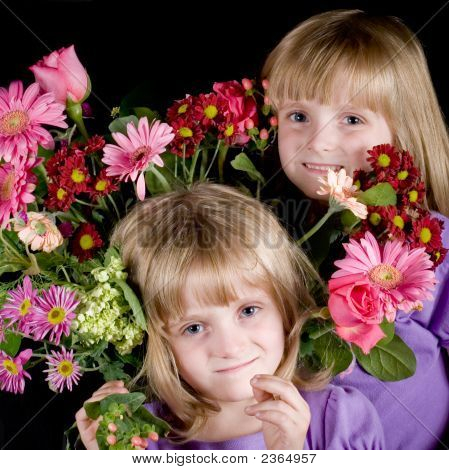 Twin Girls In Bouquet Of Flowers