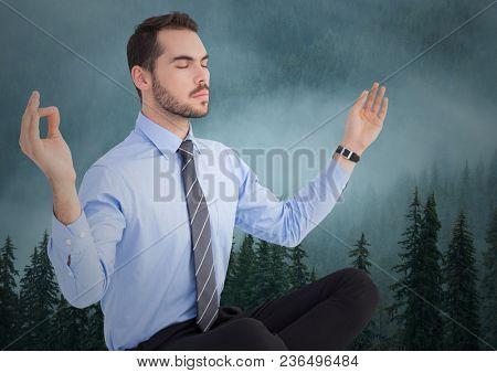 Business man meditating against foggy trees