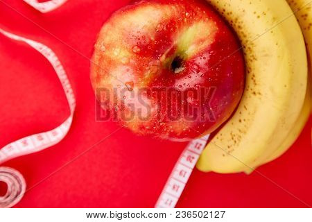 Measuring Tape Wrapped Around A Red Apple And Banana