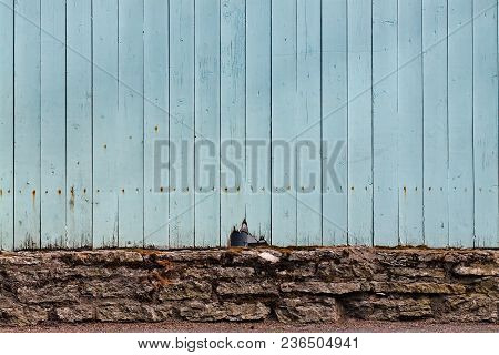 A Light Blue Fence Has A Crack On A Street In Tallinn, Estonia. The Brick Foundations And The Blue C
