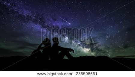 The Milky Way With The Women And Man On The Mountain. Landscape With Night Sky With Stars And The Si