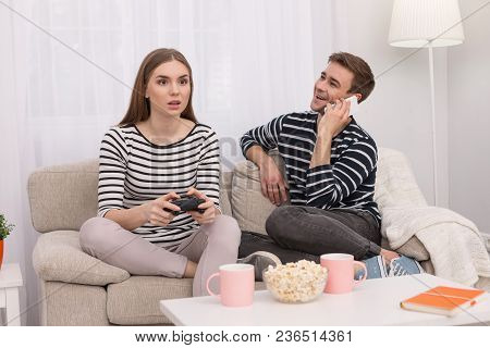 Favourite Game. Concentrated Involved Woman Playing A Game And Her Boyfriend Talking On The Phone
