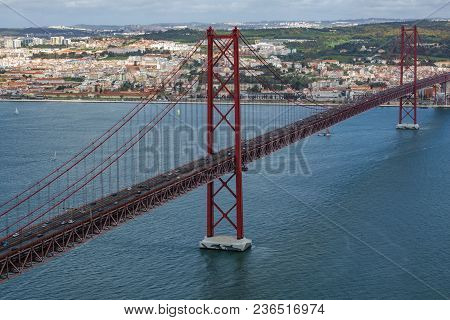 The 25 De Abril Bridge Aerial View, A Bridge Connecting The City Of Lisbon To The Municipality Of Al