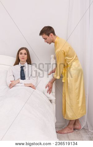 Love You. Obedient Loving Boyfriend Wearing A Bathrobe And Making His Woman Comfortable In Bed