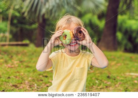 Funny Boy With Donut. Child Is Having Fun With Doughnut. Tasty Food For Kids. Happy Time Outdoor Wit