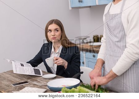 I Love Coffee. Cheerful Dominant Woman Drinking Coffee While Her Boyfriend Cooking