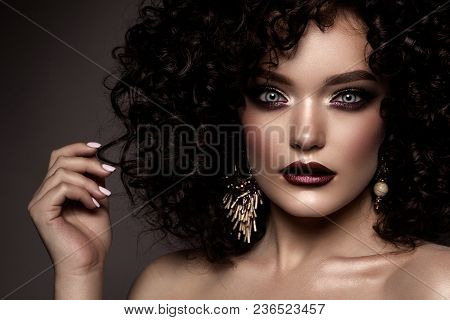 Beauty young woman with curly small and long hair. Permed hair. Glamour lady, Beautiful Girl on gray background. Portrait. Wavy Hair, perfect make up. Closed eyes. poster