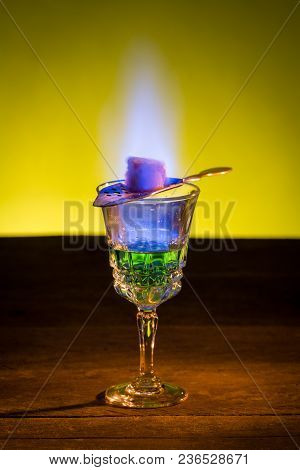Burning Sugar On Spoon In Glass Of Absinthe.