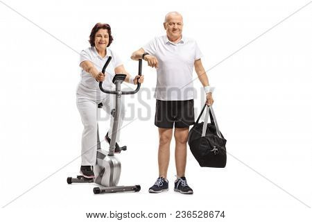 Mature woman on a stationary bike and a mature man with a sports bag isolated on white background poster