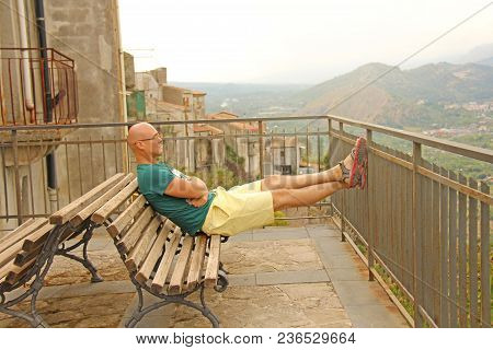 A Bald Man Is Sitting On A Bench, Looking Into The Distance, On The Horizon And Resting. Man Is A Tr