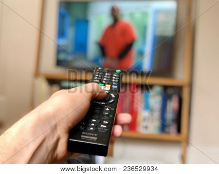 LONDON - APRIL 15, 2018: A man holding a television remote control presses a button to change the channel in London, UK.