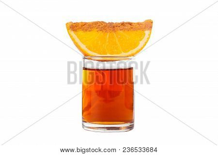A Single-colored Transparent Cocktail In A Low Glass, A Glass On Top Of A Quarter, An Orange Slice,