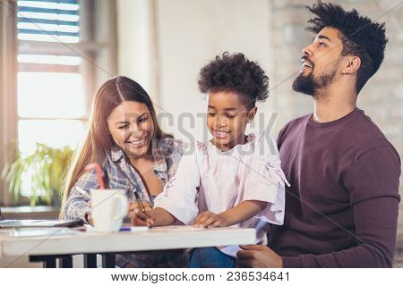 Mom And Dad Drawing With Their Daughter. Girl And Mixed Race Parents Having Fun At Home.