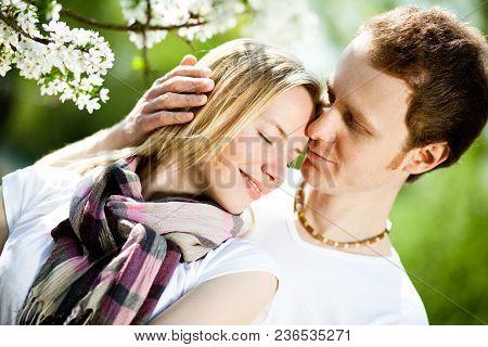 Tender Couple In Love Hug Under Blooming Flowers In Park In Spring. Happy Girl And Guy Smile Under C