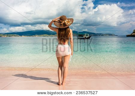 Full length rear view of an attractive young woman wearing straw hat and mesh swim skirt while looking away on the beach in Komodo Island, Indonesia