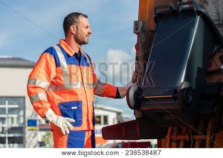 Garbage collection worker putting bin into waste truck for removal