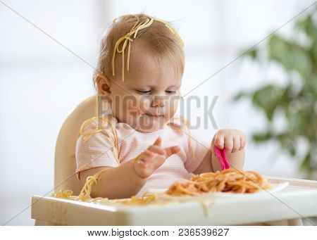 Adorable One-year Baby Toddler Try To Catch A Pasta