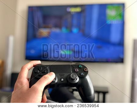 LONDON - APRIL 16, 2018: A man holds a Sony PlayStation 4 controller while playing a console video game on a television in London, UK.