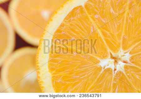 Top View Of A Fragment Of The Orange Fruit Slice On The Background Of Many Blurred Orange Slices. A