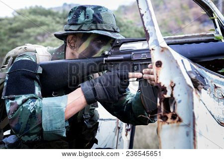 Special Forces Soldier Or Private Military Holding Gun Aiming Behind A Dilapibated Car At Field Area