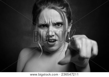 Angry Young Woman On Black Background Point On Camera, Monochrome