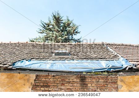 Damaged Roof With Tiles On The Old House Covered With Plastic Nylon To Protect Interior From Rain Wa