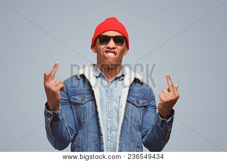 Rude Ethnic Man In Denim And Trendy Sunglasses Showing Middle Fingers And Looking Provocatively At C