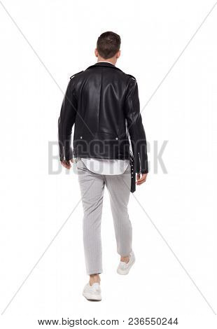 Back view of going  handsome man in a leather jacket and trousers. walking young guy . Rear view people collection.    Isolated over white background. The rocker goes into the distance