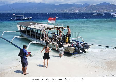 Gili Trawangan, Indonesia - October 14 2007: Divers Boarding A Wooden Outrigger Dive Boat From The B