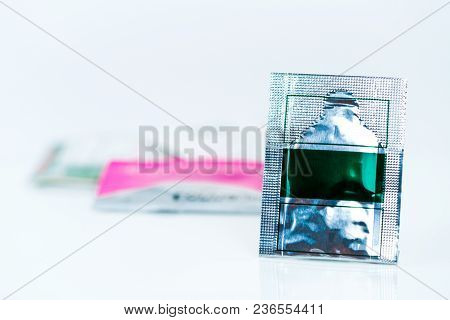 Mild Steroid Oral Paste In Aluminium Foil Sachet On Blur Background Of Sachets. Anti-inflammatory Fo