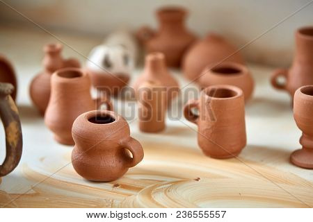 Ceramic Dishware On Worktop And Shelves In Pottery Workshop, Selective Focus, Close-up. Plain Clay M