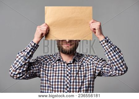 Bearded Man In Checkered Shirt Standing On Gray Background Holding Blank Brown Envelope, Covering Hi