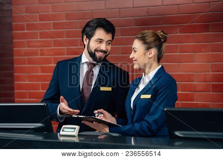 Smiling Hotel Receptionists Working Together At Counter