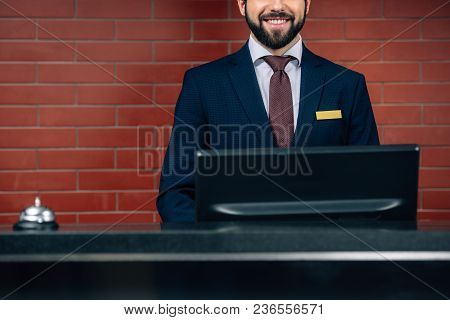 Cropped Shot Of Smiling Bearded Hotel Receptionist At Workplace