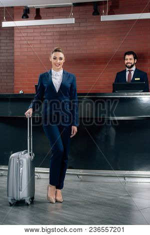 Attractive Businesswoman With Luggage Standing In Front Of Hotel Reception Counter With Administrato