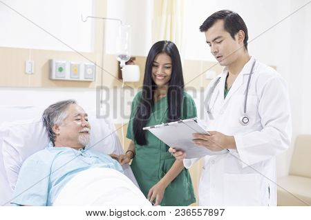 Doctor And Nurse Come To Visit Elder Patient At Hospital Room.