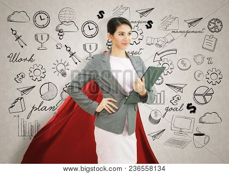 Young Confident Business Superhero Woman Wearing Red Cape Against With Strategy Background. Concept