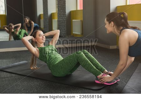 Fitness Coach Help With Doing Crunches To Woman Indoors. Young Sporty Female Friends Making Sits-up