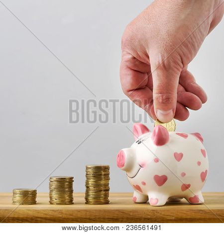 Hand Adds The Coin To The Coin Box, Saving Money.copy Space. Light Background.