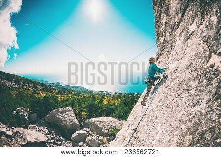 Rock Climber On A Rock. Girl Climbs The Rock On The Background Of A Beautiful Mountain Landscape And