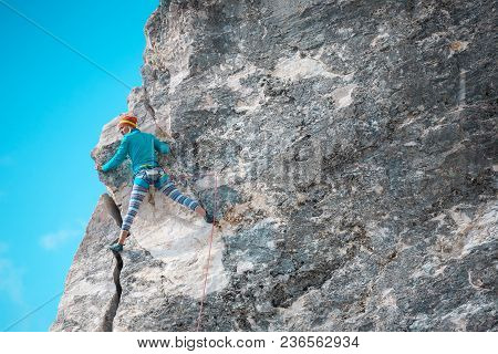 Rock Climber On A Rock. Woman Climbs The Rock On The Background Of A Beautiful Sky With Clouds. Acti